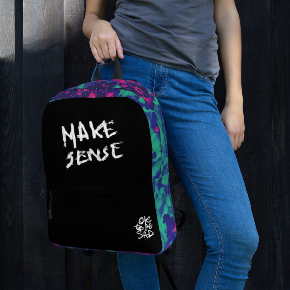Model holding MAKE SENSE Backpack